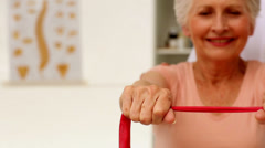 Nurse showing elderly patient how to use resistance band Stock Footage