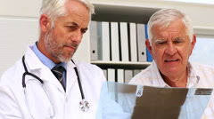 Doctor explaining an xray to senior patient - stock footage