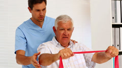 Male nurse showing elderly patient how to use resistance band Stock Footage
