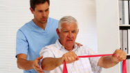 Stock Video Footage of Male nurse showing elderly patient how to use resistance band