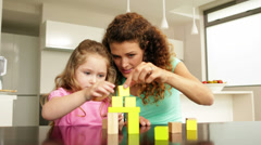 Mother and daughter playing with building blocks at the table Stock Footage