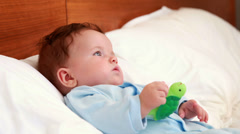 Baby boy in babygro lying on bed Stock Footage