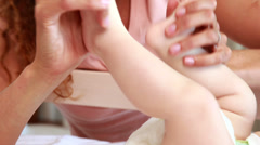 Smiling mother playing with baby sons feet in his crib Stock Footage