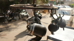 Painted Steel Teapots Dangling on a Stand at a Streetside Tea Cafe Stock Footage