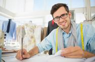 Stock Photo of Smiling male fashion designer working on his designs