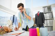 Stock Photo of Fashion designer working on his designs while on call