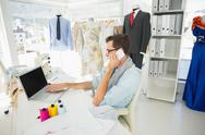 Stock Photo of Male fashion designer using laptop and cellphone
