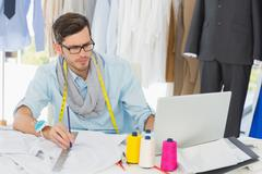Stock Photo of Male fashion designer working on his designs
