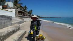 Vietnamese woman in national headdress is on the beach with bags. - stock footage