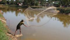 Fisherman casts his net into the river. Stock Footage