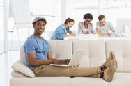 Man using laptop with colleagues in background at creative office Stock Photos