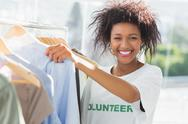 Stock Photo of Smiling female volunteer by clothes rack