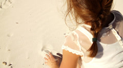 Girl is painting a heart into the sand Stock Footage