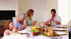 Extended family saying grace before christmas dinner Stock Footage