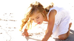 Little Girl is painting in the sand Stock Footage
