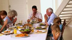 Laajennettu perhe rukoilee yhdessä ennen illallista Arkistovideo