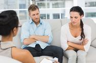 Stock Photo of Unhappy couple with arms crossed at therapy session