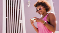 Stock Video Footage of Afro haired girl texting on smartphone