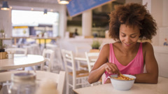 Girl eating french fries in restaurant - stock footage