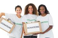 Stock Photo of Happy team of volunteers smiling at camera holding donations boxes