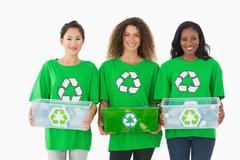 Team of environmental activists holding boxes smiling at camera Stock Photos