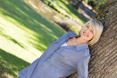 Woman leaning on tree trunk in parkland - stock photo