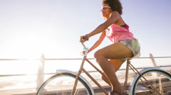 Teenage girl riding her bike near beach Stock Footage