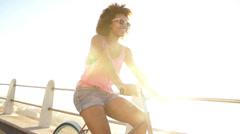 Girl riding a bike near ocean Stock Footage