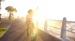 Girl riding a bike on seaside - stock footage