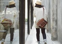 Fashion girl with leather bag at concrete alleyway Stock Photos