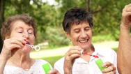Stock Video Footage of Senior ladys blowing bubbles