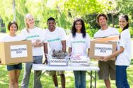 Stock Photo of Confident volunteers with donation boxes