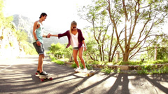 Couple holding hands on skateboard - stock footage