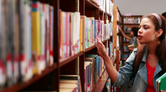 Stock Video Footage of Smiling student picking out a textbook in library