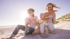 Family at beach eating watermelon Stock Footage