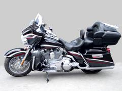 The big black brilliant motorcycle on a grey background, a side view. Stock Photos