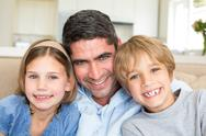 Stock Photo of Father and children smiling at home