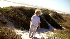 Boy walking in sand on beach Stock Footage