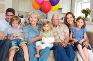Stock Photo of Multigeneration family celebrating girls birthday