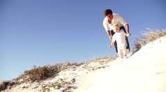 Father and son running down dune Stock Footage