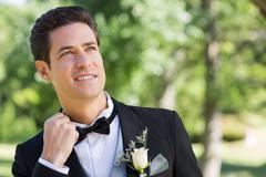 Nervous groom in garden - stock photo