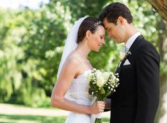Stock Photo of Newly wed couple with head to head in garden