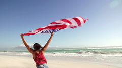 Girl waving american flag on beach - stock footage