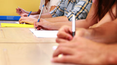 Students sitting in a line taking notes in classroom Stock Footage