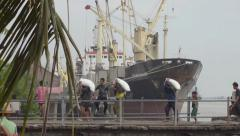 PORT, QUAY & JETTY:  ASIA - Row of porters carry sacks at port with big ship Stock Footage