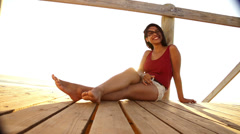 Young woman sitting on beach boardwalk Stock Footage