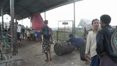PORT, QUAY & JETTY:  ASIA - Many porters carry cargo and worker rolls oil drum Stock Footage
