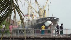 PORT, QUAY & JETTY:  ASIA - Porters carry sacks across a gangway near ship Stock Footage