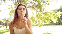Woman blowing dandelion in park in slow motion Stock Footage