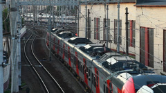 Passenger train in the web of electrical wires - stock footage